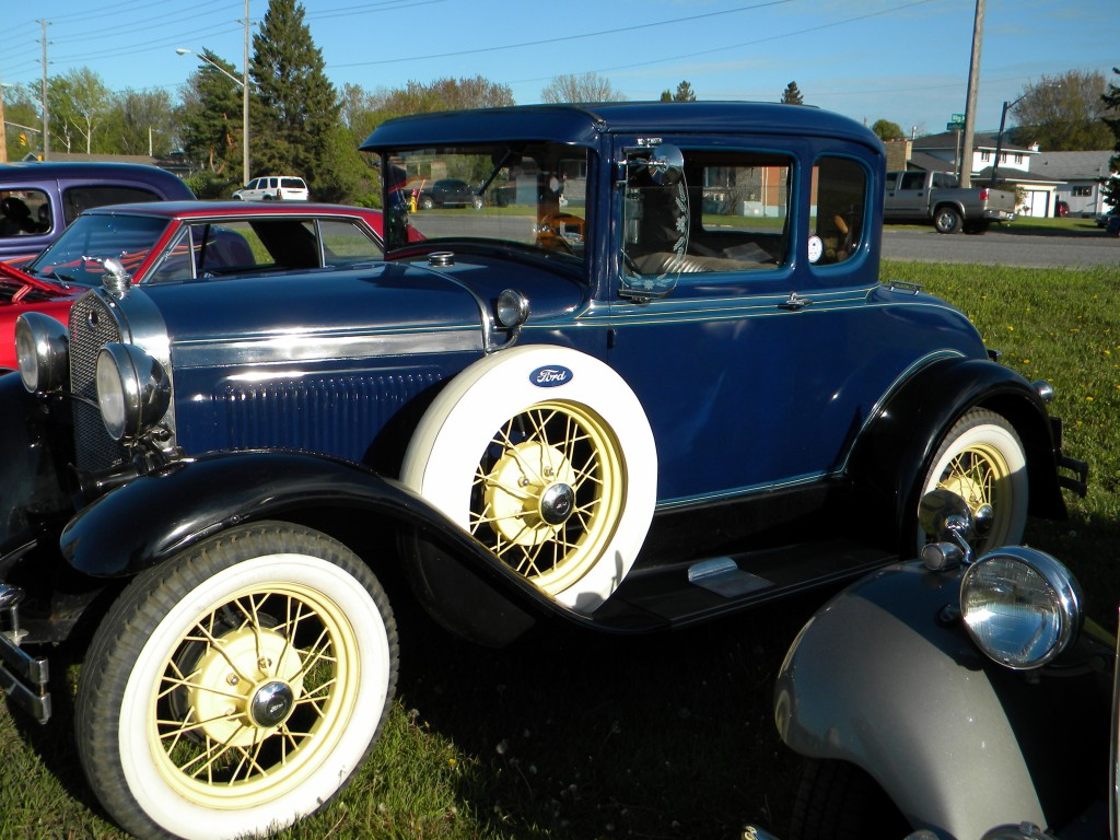 An old blue antique car with whitewall tires