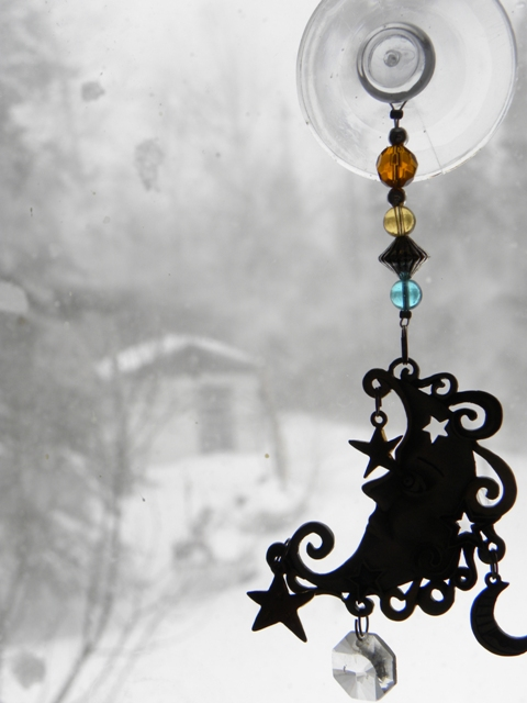 A black suncatcher with winter scene