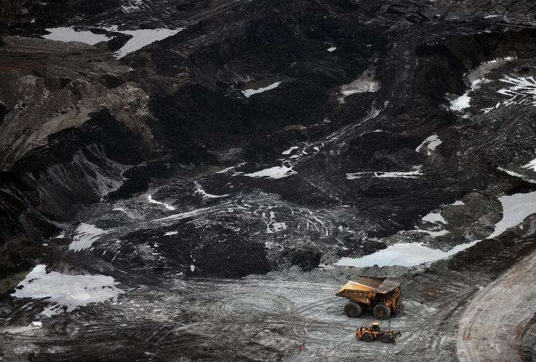 A huge pit, strip-mining with gigantic minint truck andequipment